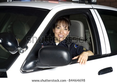 a female police officer sitting in her patrol car during a night shift.