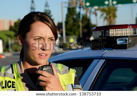 A female police officer standing next to her car about to talk on the radio.