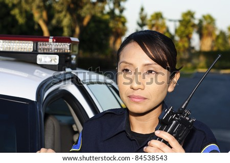 a female police officer standing next to her unit while she's about to talk on her radio.