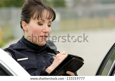 a female police officer writes a ticket while standing next to her patrol car.