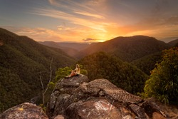 A female relaxes on a rock with stunning wilderness valley views westwards towards the beautiful sunset.  Blue Mountains Australia
