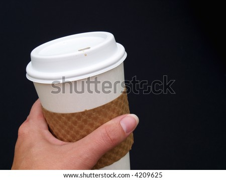 a female\'s hand holding a disposable paper coffee cup