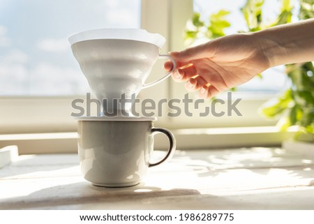 A female's hand removes a funnel with a filter from the cup. Alternative mothod of coffee brewing. Filter V60 with brewed ground coffee. Side view. Photo stock ©