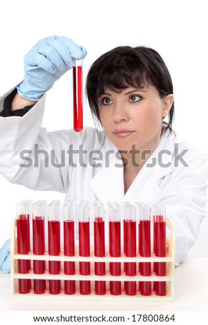 A female scientist sitting at desk with rack of  test tubes