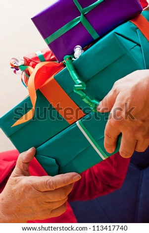 a female Senior sits and gets or give many gifts closeup