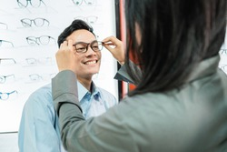 a female shop assistant puts glasses on a male customer while at the optician