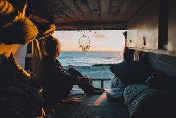 A female sitting in the van and admiring the sunset in the beach
