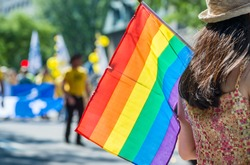 A female spectator is holding the gay rainbow flag at the 2015 Gay Pride Parade in Montreal.
