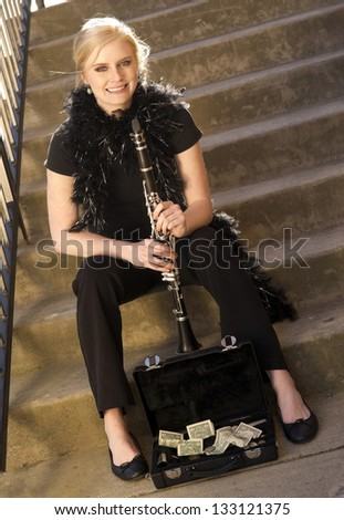 A Female Street Performer Sits on Steps Near Clarinet Case With Tips