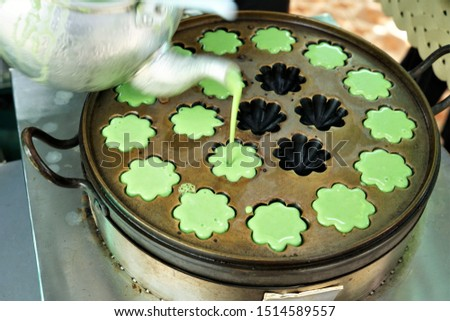 A female street vendor is pouring raw pancake into  the holes in the pan,  Mortar Pandan dessert,  street food. vegetarian food, vegetarian festival