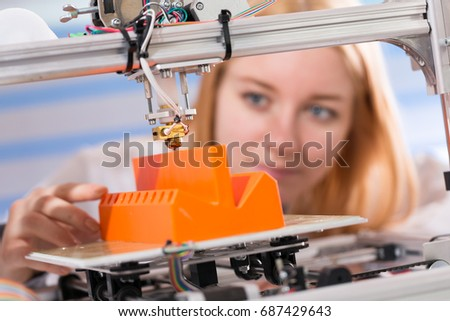 A female student or laboratory assistant in the automation laboratory is debugging the work of the 3d printer. 3d printer is a device for modeling 3D objects #687429643