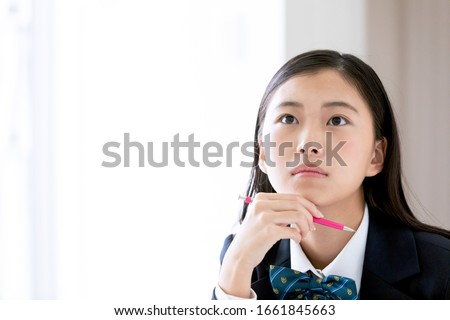 A female student thinking while studying ストックフォト ©