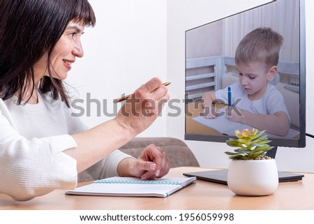 A female teacher sitting in front of a computer monitor holds a pen and teaches a small child to write, close-up. A small child is learning to write. Online learning concept. Stock photo ©
