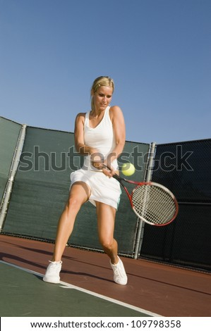 A female tennis player hitting a shot