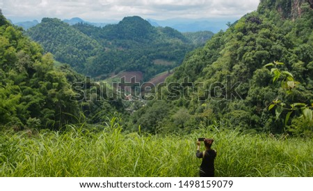 A Female Tourist Is Taking Photo of Mountains and Hills with Her Mobile Phone / Smart Phone at The Scenic View Point of Mae Hong Son Province, Northern Thailand.