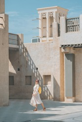 A female tourist wearing a maroon turban and a yellow backpack walks through the old narrow streets of Bur Dubai and Creek. Travel and sightseeing spots