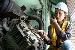 A female train engineer using wakie talkie to point out a machine checkpoint in a train's engine room. Train engineer concept.