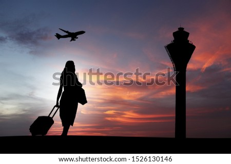 A female traveller lugging her luggage in an airport against a candy colored skyline.