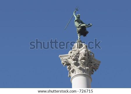 A female victory statue, atop a column, raises a trident into the air.