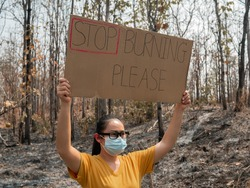 A female volunteer holding a nature conservation banner in area of the burning forest and firefighters extinguish fires. Human responsibility and protection of nature. World Environment Day.