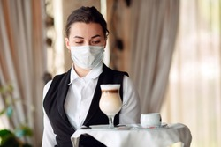 A female Waiter of European appearance in a medical mask serves Latte coffee