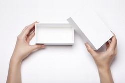 A female(woman, girl) two hands hold and open the empty(blank) white box isolated white, top view at the studio.