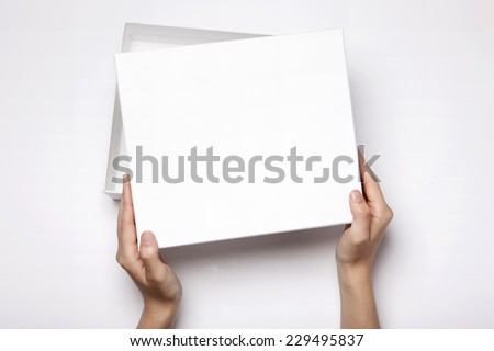 A female(woman, girl) two hands hold and open the empty(blank) white box isolated white, top view at the studio. #229495837