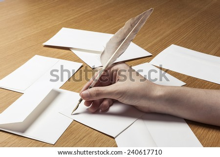 A female(woman) hand hold a feather quill pen with letter paper and envelopes on the wood office desk(table) at the studio.