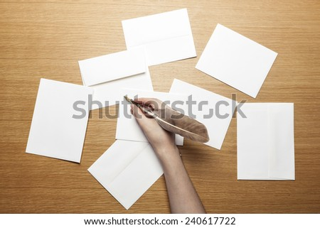 A female(woman) hand hold a feather quill pen with letter paper and envelopes on the wood office desk(table) top view at the studio.