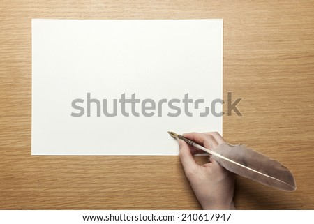 A female(woman) hand hold a feather quill pen with letter paper on the wood office desk(table) top view at the studio.