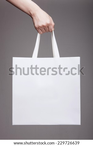 A female(woman) hand hold a white shopping bag(paper bag) and white strings at the studio.