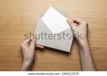 A female(woman) hand hold(open) a envelope and post card on the wood desk, top view at the studio.