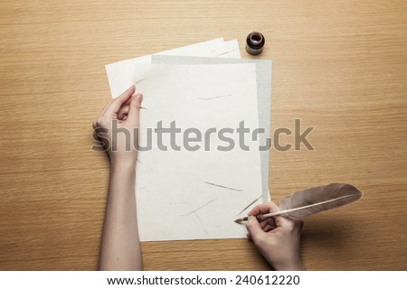 A female(woman) hand hold(write) a feather quill pen on the letter paper and wood desk(table) top view at the studio.