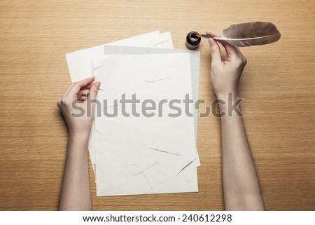 A female(woman) hand hold(write) a feather quill pen with ink on the letter paper and wood desk(table) top view at the studio.