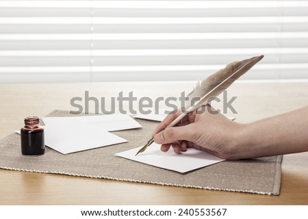 A female(woman) hand hold(write) a vintage feather quill pen with envelope and letter, ink on the office desk(table) behind white blind