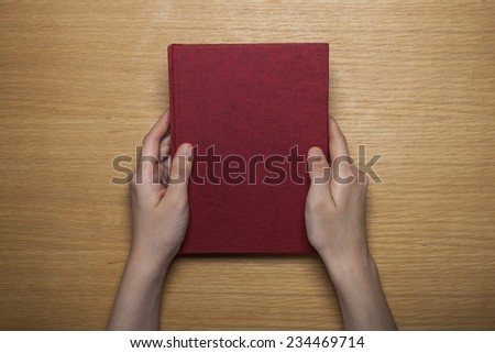 A female(woman) hands hold a blank(empty) red book(note, diary) cover on the wood desk(table), top view at the studio.