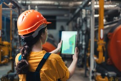 A female worker in uniform and helmet with a tablet in her hand. Rear view. In the background-boiler room. Concept of industrial production and equality.