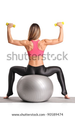 A female working out with dumb bells while sitting on a pilates ball isolated on white background