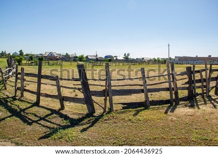 A fence in a village near a major metropolis at noon.