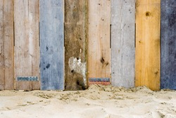 A fence on a beach made from wood which used to be part of a scaffold