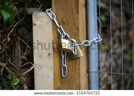 A fence that has been chained and locked with a padlock to keep people out and to keep property safe