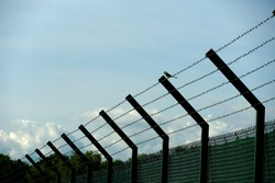 A fence with barbed wire with a bird sitting on it and clear blue sky on the background on the airport Zurich in Switzerland. It can have symbolic meaning as well.
