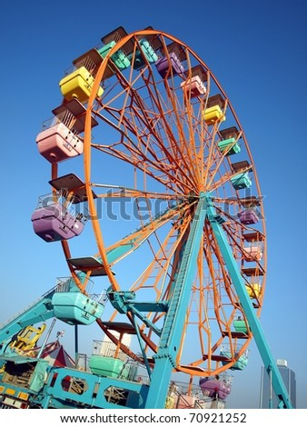 A ferris wheel with colorful cabins at a local fun fair