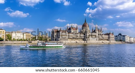 A ferry boat passes along the eastern shore of the River Danube in Budapest past the Parliament building in summertime