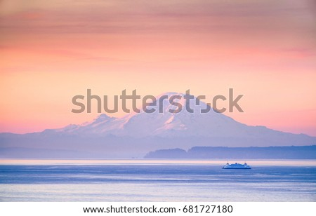 A ferry crossing the Puget Sound at sunrise with Mount Rainier in the background, Washington, USA