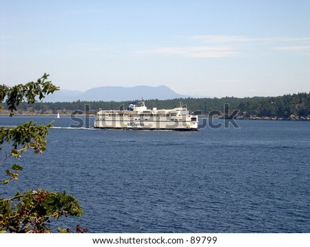 A ferry passes through a small channel during a clear day in Victoria, British Columbia.