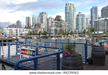 A ferry terminal in Granville island in Vancouver BC., Canada overlooking the skyline across False creek.