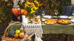 A festive autumn brunch among the yellow trees, with pumpkins, a yellow bouquet and pastries. Thanksgiving or family dinner in the backyard.