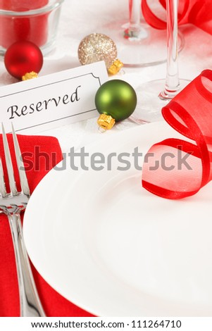 A festive red and green Christmas table setting is adorned with ribbon and ornaments leaving copy space on a white plate