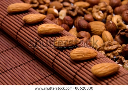 a few almonds arranged in a row on background of  different nuts